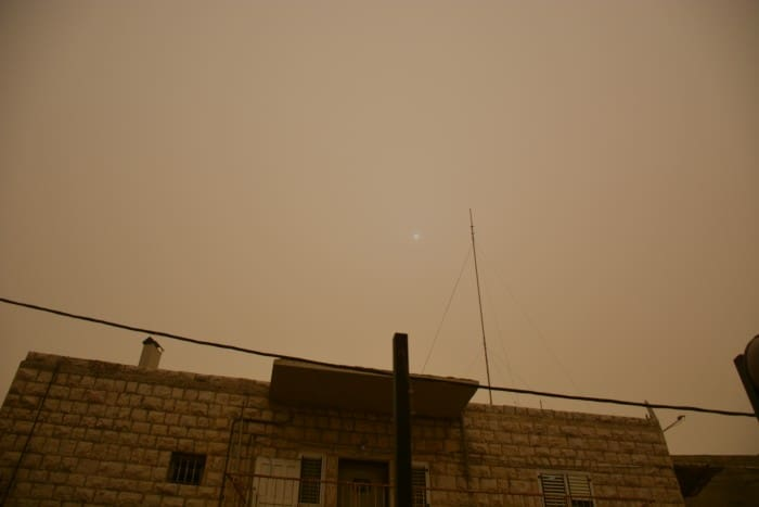 Completely unedited photo of the sun around 11am, barely visible due to the dust storm.