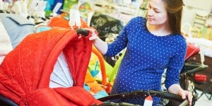 Pregnancy shopping. Pregnant woman choosing pram for newborn carriage at baby shop store