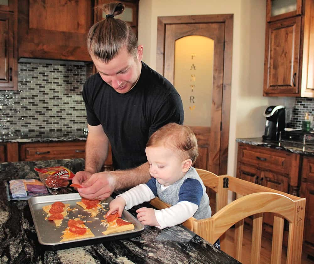 father and toddler making pizza rolls