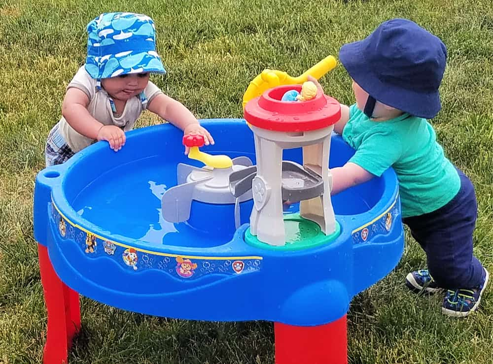 2 toddlers playing by water table