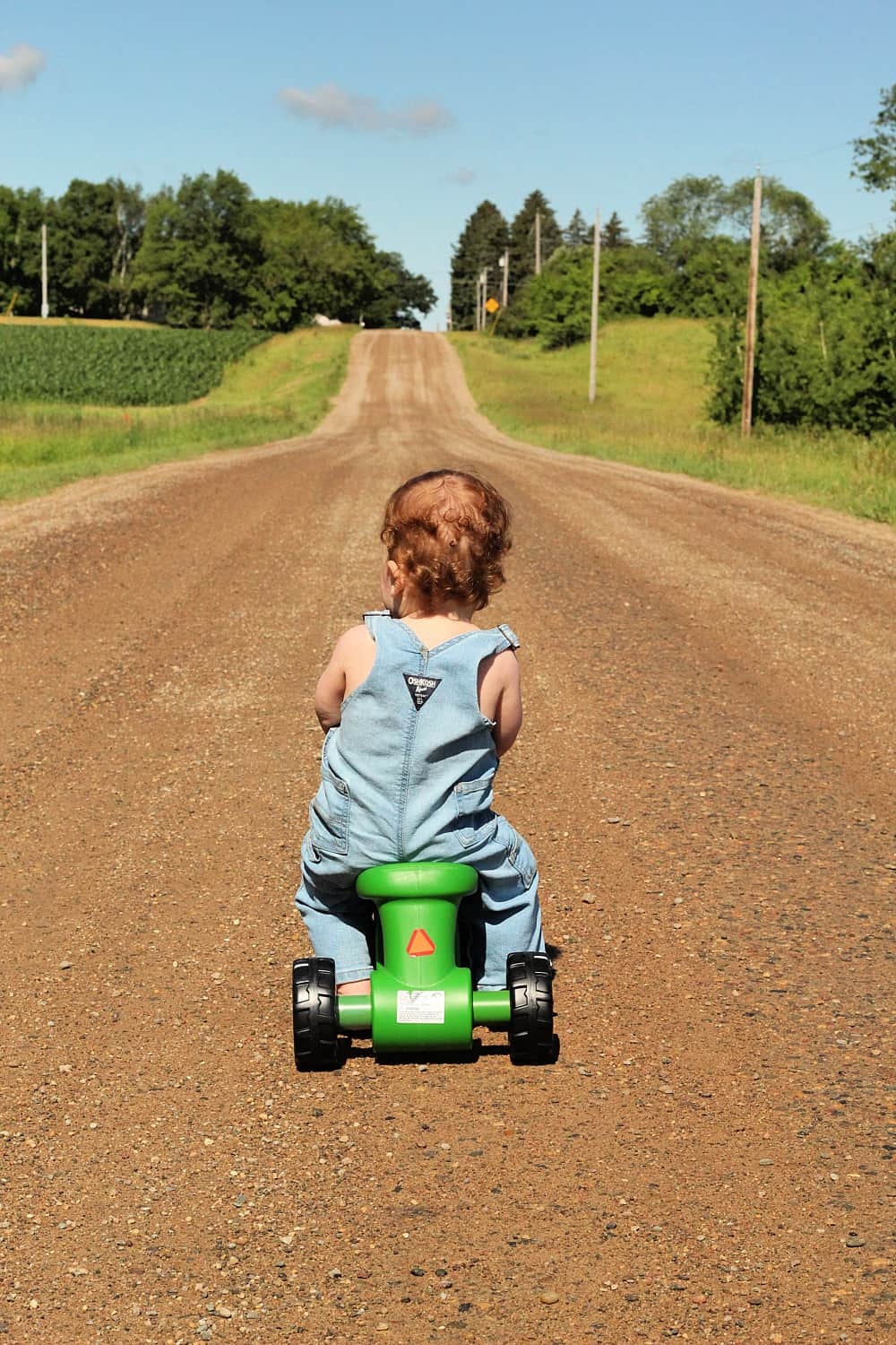 toddler on tractor toy