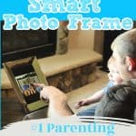 dad and son looking at digital photo frame