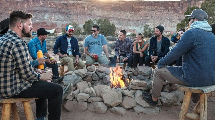 group of men sitting around a fire