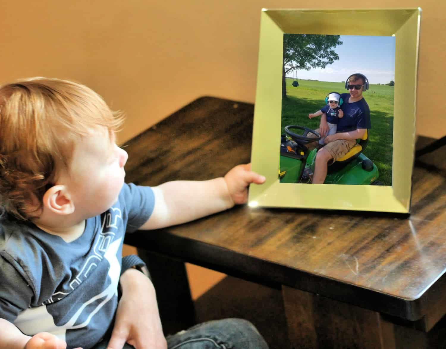toddler boy looking at picture frame