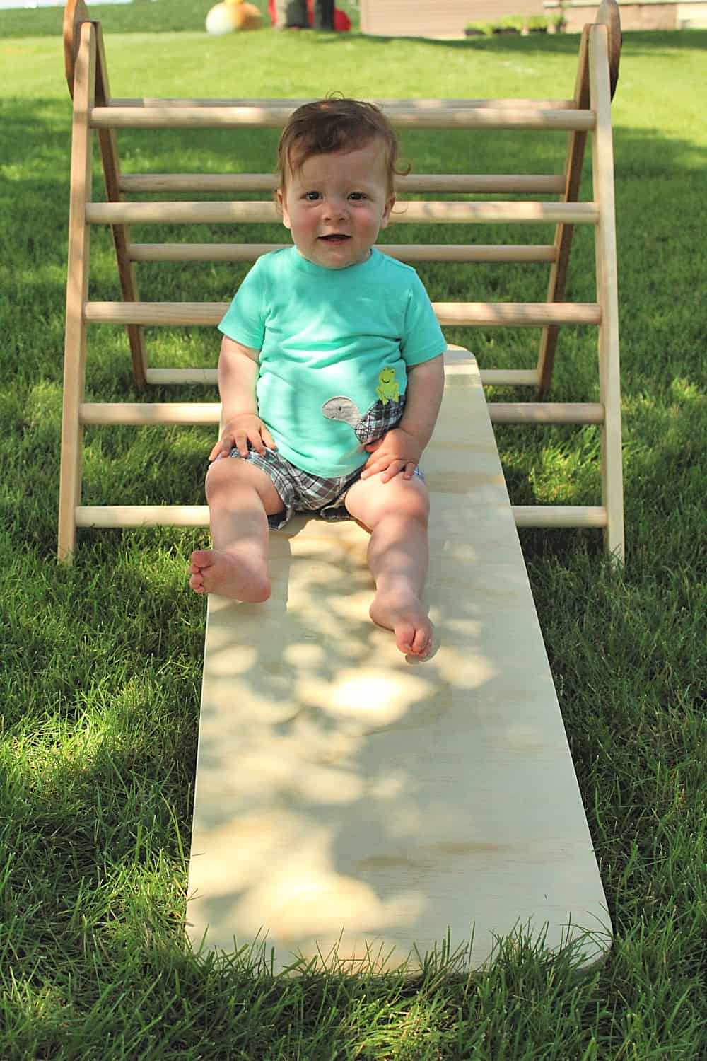 toddler climbing wooden triangle