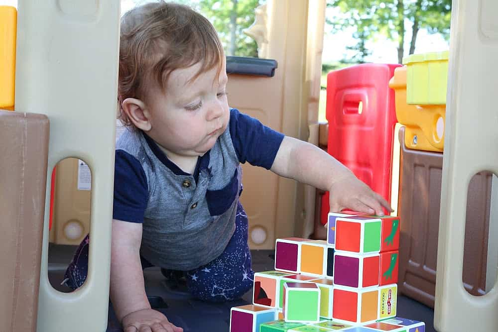 toddler playing with blocks in playhouse