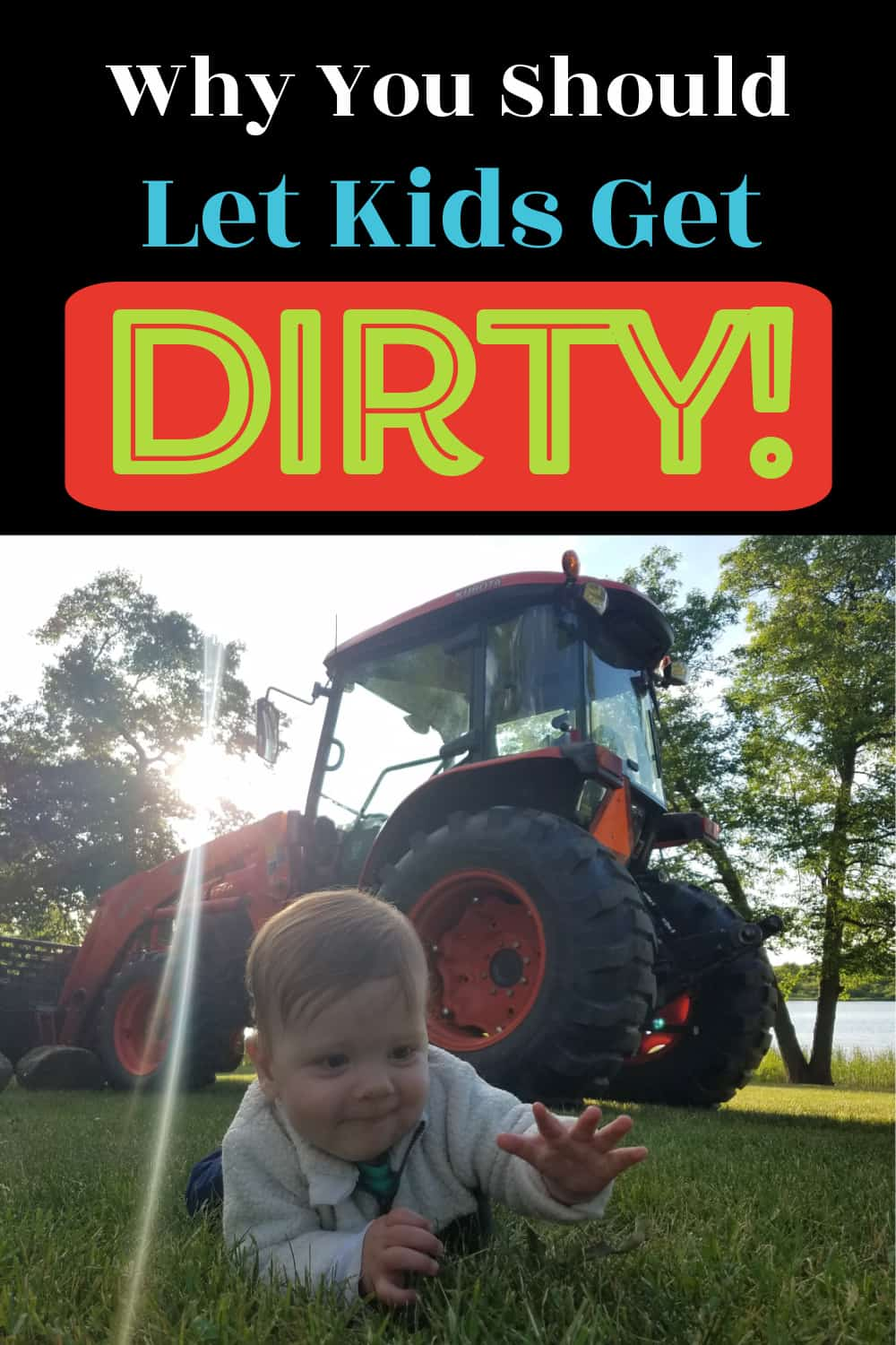 Toddler boy laying on grass in front of tractor
