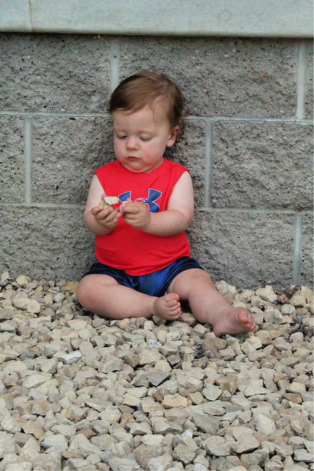 toddler sitting in rock bed holding rocks