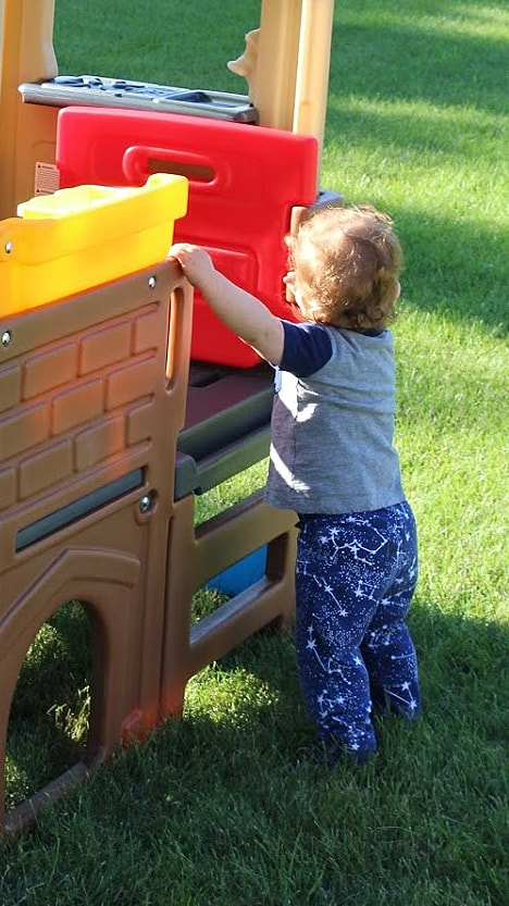 toddler standing next to playhouse