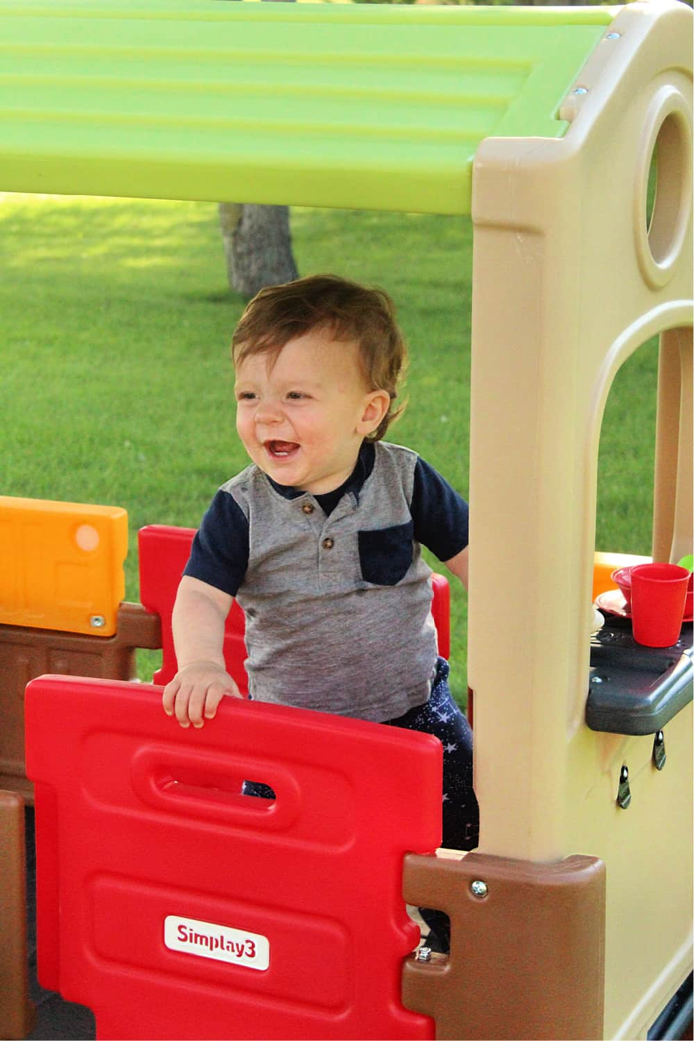 toddler smiling in playhouse