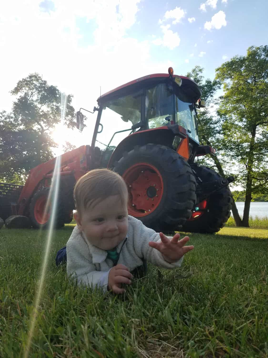 toddler on grass by tractor