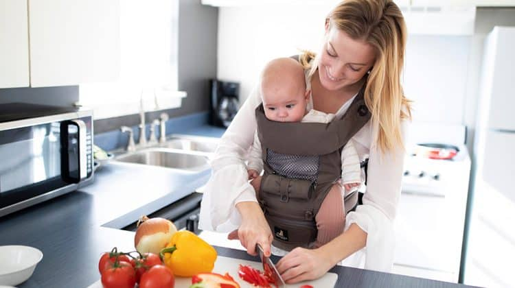 women cutting peppers in kitchen with baby in carrier