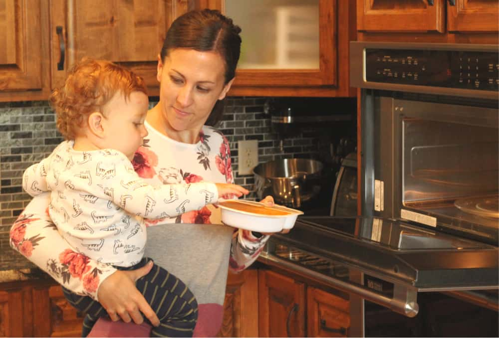 women holding toddler and meal near microwave.