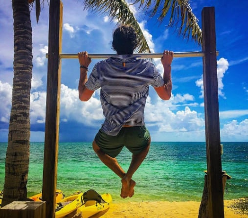 Man doing pull ups on beach -- Rhoback Performance Polos Giveaway