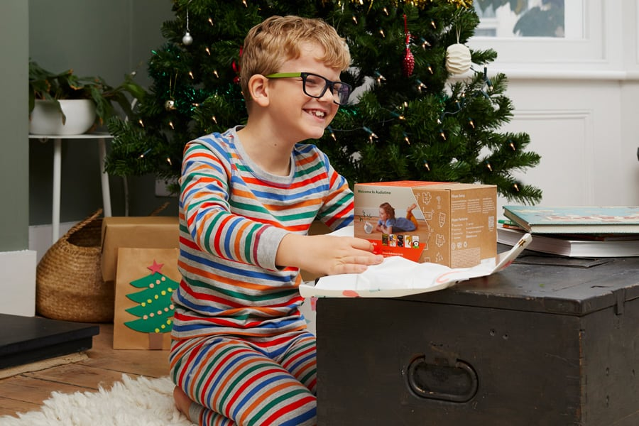 Child in front of Christmas tree with Yoto speaker