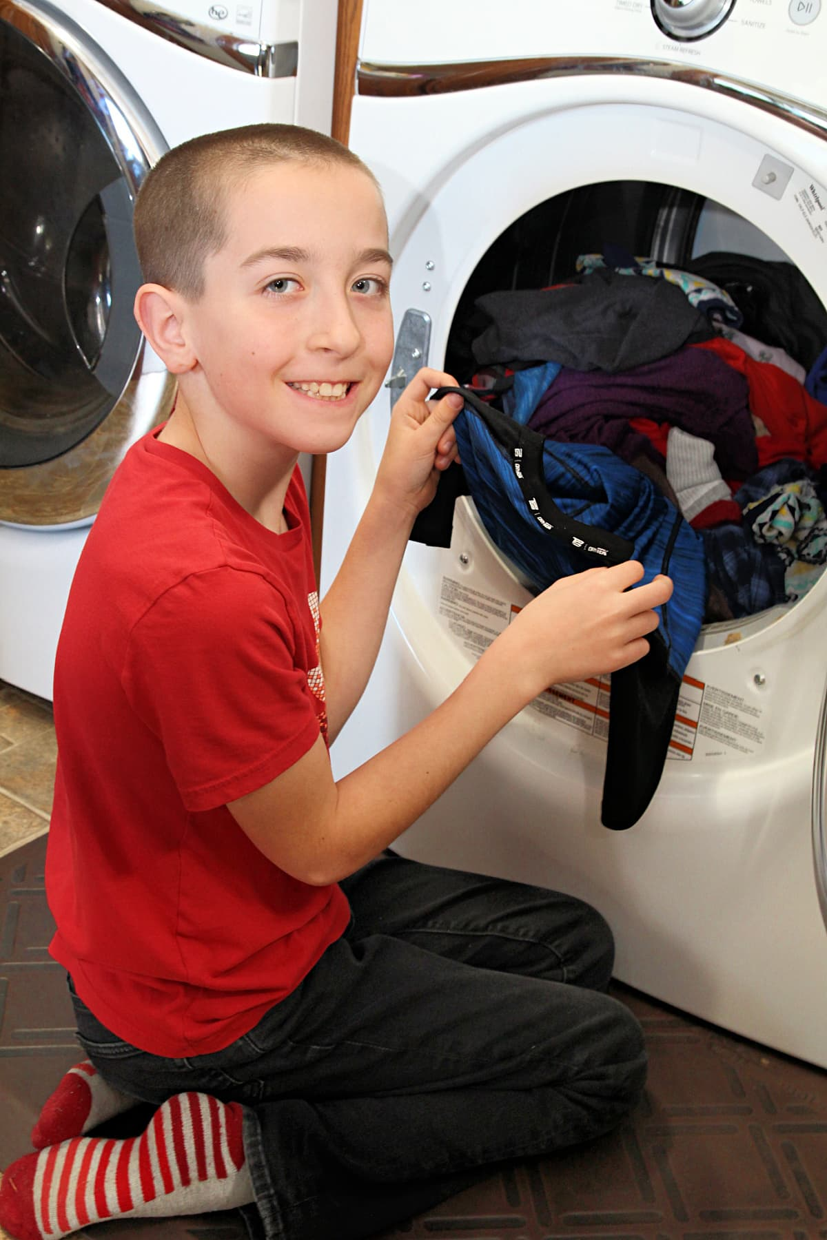 boy folding clothes - Family Laundry Tips - Everyday Chores Made Easy With Whirlpool Corporation's Improving Life at Home Hub