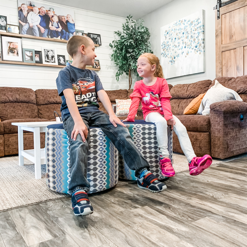 brother and sister sitting in living room - pediped shoes