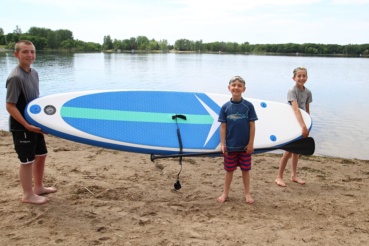 kids carrying paddle board - Soozier Inflatable Paddle Board Review + Discount