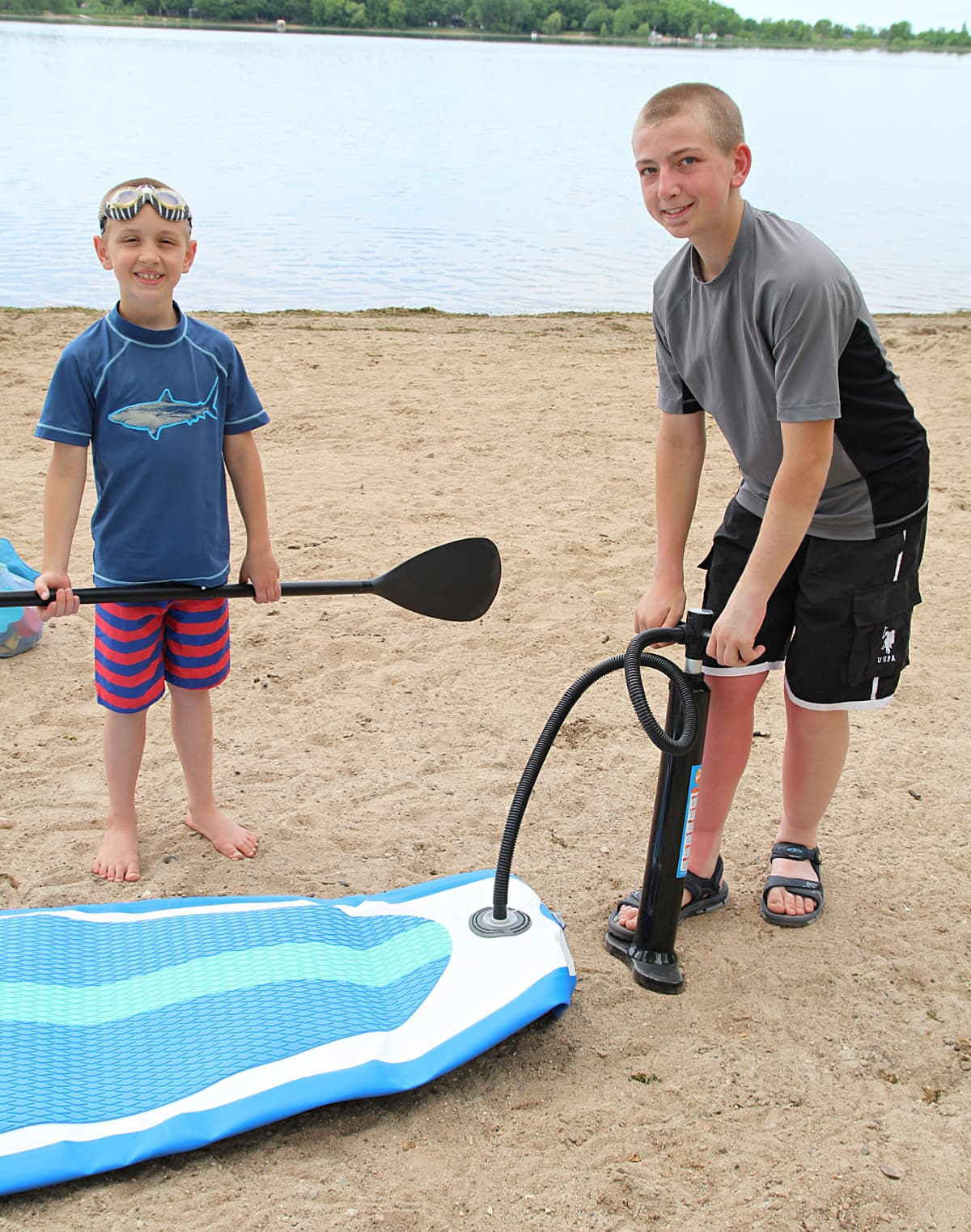 kids inflating a paddle board -  Soozier Inflatable Paddle Board Review + Discount