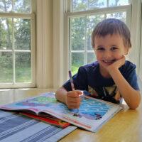 preschool boy doing homeschool work at table